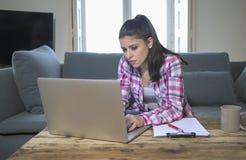 Mulher latin atrativa e furada nova em seu 30s que trabalha em casa a sala de visitas que senta-se no sofá com o laptop no olhar  imagens de stock