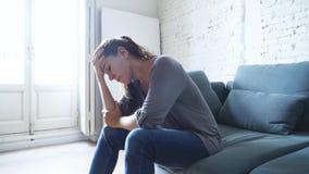 Mulher latin atrativa nova que encontra-se em casa sofá da sala de visitas que sente a depressão de sofrimento cansado e preocupa vídeos de arquivo