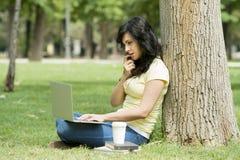 Mulher latin atrativa que trabalha e que studing em seu latop em um parque verde foto de stock