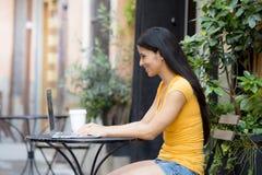 Mulher latin atrativa que trabalha fora no portátil imagens de stock
