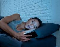 A mulher latin atrativa viciado ao telefone celular tarde em nigh coloca dentro a vista sem sono e o Internet fotografia de stock