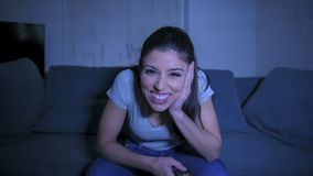 mulher latin bonita e feliz nova em seu 30s que guarda o telecontrole da tevê que aprecia em casa o programa televisivo de observ foto de stock royalty free