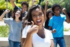 Mulher latin Cheering com os homens caucasianos e afro-americanos imagem de stock royalty free