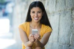 Mulher latin nova feliz que fala e que texting no telefone esperto fotos de stock royalty free