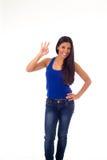 A mulher latino-americano atrativa nova na parte superior ocasional e as calças de brim que sorriem doação feliz e alegre manusei Imagens de Stock Royalty Free