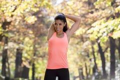 A mulher latino-americano bonita do esporte no sportswear que estica a flexibilidade fazendo feliz em seguida de sorriso do corpo fotografia de stock
