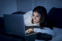 Mulher latino-americano bonita nova no riso da cama em casa feliz no laptop na noite Foto de Stock