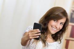 Mulher latino-americano bonita nova que usa sua pilha Fotos de Stock