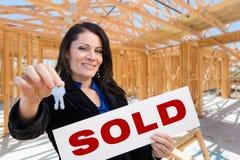 Mulher latino-americano com chaves e sinal vendido no local dentro da casa nova C imagens de stock