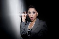Mulher latino-americano consideravelmente nova que usa o vidro ao eavesdr Imagem de Stock Royalty Free