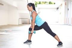 Mulher latino-americano desportiva no azul que demostrating a rotina do enfileiramento com peso azul fora Imagem de Stock