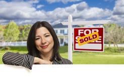 Mulher latino-americano na frente do vendido para o sinal da venda, casa Imagem de Stock Royalty Free