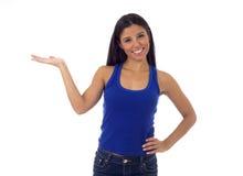 Mulher latino-americano na parte superior ocasional e calças de brim que sorriem produto de apresentação feliz e alegre Imagens de Stock Royalty Free