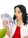 Mulher latino-americano nova bonita chocada que guarda o dinheiro Fotografia de Stock