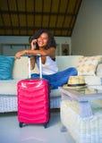 Mulher latino-americano preta atrativa e feliz nova em casa com a mala de viagem que fala com o amigo no telefone celular que sen imagens de stock
