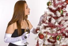 Mulher latino-americano que olha uma árvore de Natal decorada Imagem de Stock