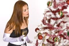 Mulher latino-americano que olha uma árvore de Natal decorada Imagens de Stock Royalty Free