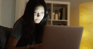 Mulher latino-americano que usa o portátil na noite foto de stock royalty free