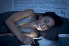 Mulher latino bonita nova na cama tarde na noite que texting usando o sono de queda cansado do telefone celular fotografia de stock royalty free