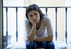 Mulher latino desesperada que senta em casa o balcão que olha depressão de sofrimento destruída e comprimida Imagem de Stock