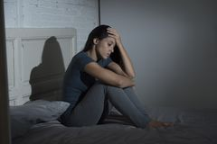A mulher latino triste e deprimida bonita que senta-se na cama frustrou em casa a depressão de sofrimento foto de stock royalty free