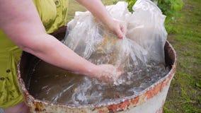 A mulher lava em um grande tambor do filme transparente da água Mergulha-o na água e retira-o outra vez housework filme