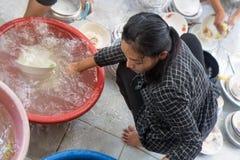 A mulher lava pratos foto de stock