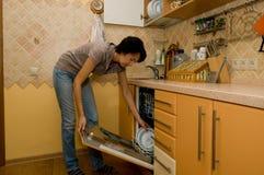 A mulher lava utensílios de mesa Fotografia de Stock