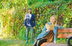 A mulher leu livro interessante que senta-se no banco de parque Livro interessante Homem que anda no parque Reuni?o de Forst em p foto de stock royalty free