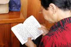 A mulher leu o scripture budista fotografia de stock royalty free