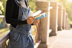 A mulher leu um livro no jardim para a educação imagem de stock