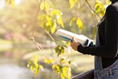A mulher leu um livro no jardim para a educação fotografia de stock
