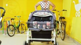 A mulher leva embora o carrinho de bebê cinzento dos gêmeos do conforto da loja vídeos de arquivo