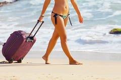 A mulher leva sua bagagem no Sandy Beach Fotografia de Stock Royalty Free