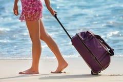 A mulher leva sua bagagem perto do oceano azul Foto de Stock Royalty Free