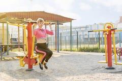 A mulher levanta em um simulador dos esportes fotos de stock
