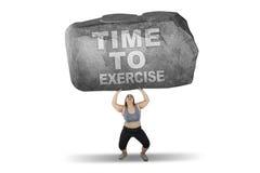 A mulher levanta a pedra com hora de exercitar a palavra Fotografia de Stock Royalty Free