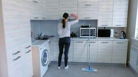 A mulher limpa a mobília na cozinha, vídeo do timelapse