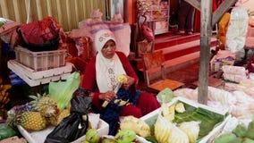 A mulher limpa o abacaxi no mercado do alimento em Jakarta, Indonésia vídeos de arquivo