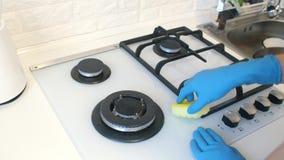 A mulher limpa o fogão de gás filme