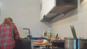 A mulher limpa o lixo na cozinha a menina cozinha em casa as queimaduras que do fogão o gás está a bandeja video estoque