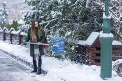A mulher limpa a pá da neve fotografia de stock royalty free