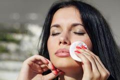 A mulher limpa sua cara Imagens de Stock Royalty Free