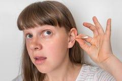 A mulher limpa suas orelhas com o cotonete de algodão imagens de stock royalty free