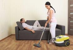Mulher limpando e homem de descanso imagem de stock