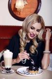 Mulher lindo com o cabelo louro que senta-se no café com café e sobremesa Fotografia de Stock Royalty Free