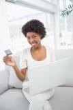 Mulher lindo de sorriso que usa seu cartão de crédito para comprar em linha Foto de Stock