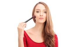 Mulher lindo que aplica a composição com uma escova Fotos de Stock