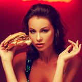 Mulher lindo que come o Hamburger no clube noturno foto de stock