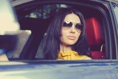 Mulher lindo que conduz um carro luxuoso foto de stock